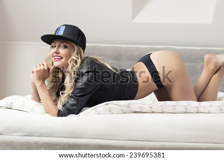 glamour indoor portrait of sexy blonde girl in provocative pose on bed with black panties, leather jacket and sport cap. Smiling and looking in camera  - stock photo