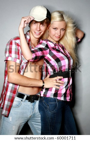Glamour pair poses on a gray background - stock photo