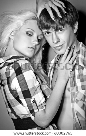 Glamour pair poses on a gray background (monochrome) - stock photo