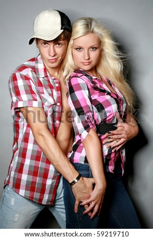 Glamour pair poses on a grey background - stock photo