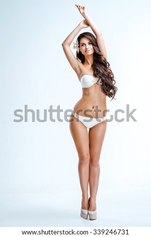 Glamour picture of beautiful slim young woman with long curly hair on white background. Girl wearing white swimsuit and high heels shoes. Brunette smiling with flower in her hair - stock photo
