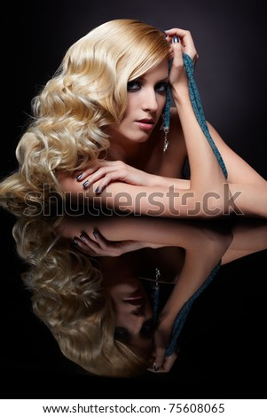 glamour portrait of beautiful curly blonde girl and her reflection in mirror table on dark