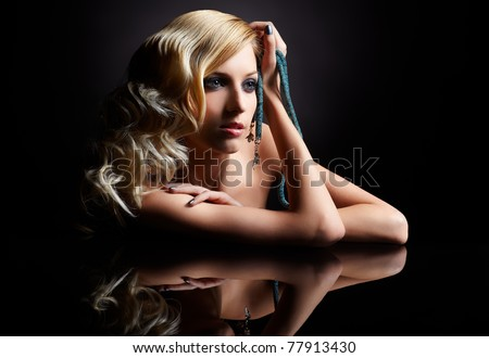 glamour portrait of beautiful curly blonde girl and her reflection in mirror table on dark - stock photo