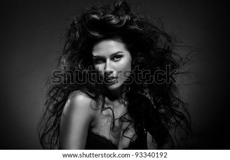 Glamour portrait of sexy beautiful young woman with long black hair model posing on dark background - stock photo