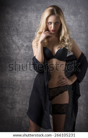 glamour portrait of sexy blonde girl with dark lingerie and sexy lace stockings, provocative expression looking in camera  - stock photo