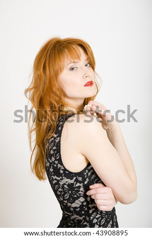 Glamour portrait of sexy red haired woman in black dress and juicy red lips. gray background - stock photo