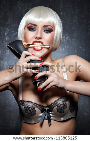 glamour portrait of sexy young woman with bright makeup in bra biting gold heel of shoe against dark background - stock photo