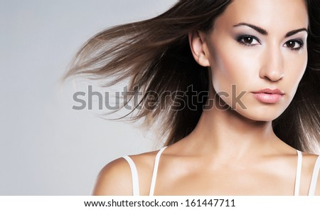Glamour portrait of young and attractive woman with makeup and romantic wavy hairstyle - stock photo