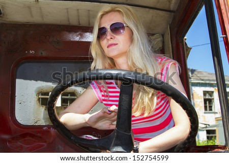 Glamour pretty girl driving a broken truck - stock photo