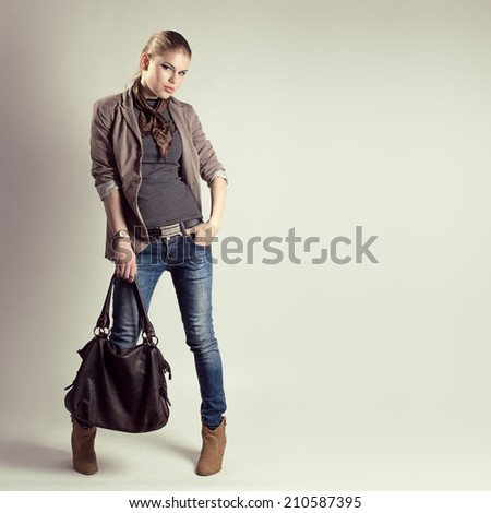Glamour pretty girl holding stylish leather bag wearing high heels. Young attractive blond female model in fashionable casual clothes posing in studio.    - stock photo