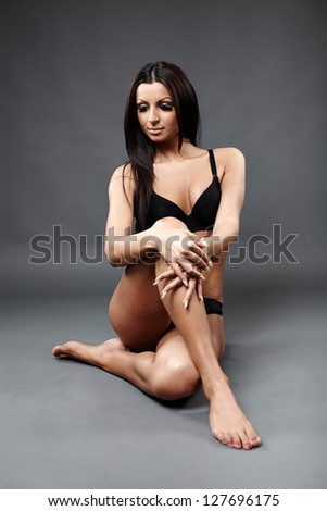 Glamour profile of perfect Latin dancer in sexy lingerie lying on the ground over gray background - stock photo