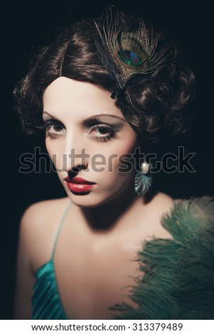 Glamour retro 1920s young woman holding a fan. Against black background.