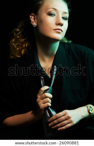 Glamour seductive woman in earrings and black shirt uleashes the tie, looking at camera. Low-key studio portrait.