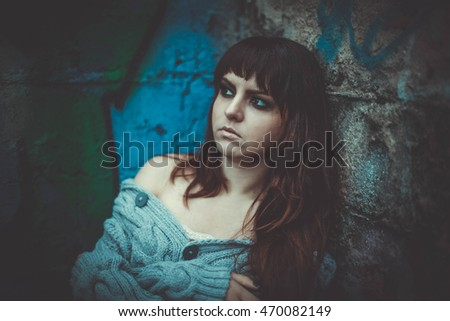 Glamour sensual young girl in sweater stand by wall. Cold season.Warm clothes. Girl with long hair and make up. Hay background, autumn, yellow colors