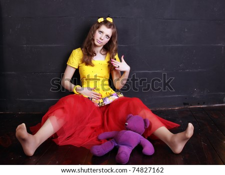 Glamour woman doll near black brick wall - stock photo