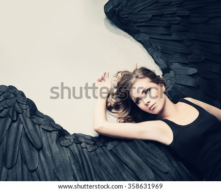 Glamour Woman Fashion Model Black Angel Relaxing - stock photo
