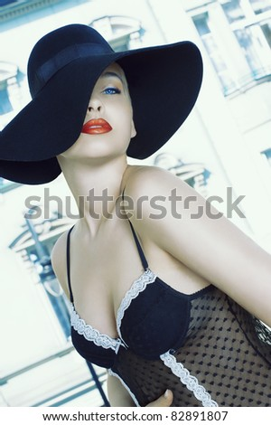 glamour woman in a fashion shot wearing a black hat and bra outside of the window with old building in background