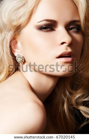 Glamour woman model with sexy evening make-up & chic shiny jewellery. Accessories: gold earrings with brillian. Fashionable close-up portrait. - stock photo