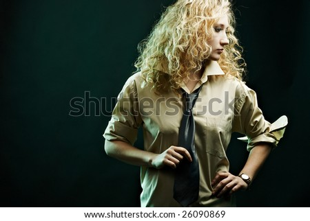 Glamour woman portrait in shirt holding her tie. Specific lighting. - stock photo