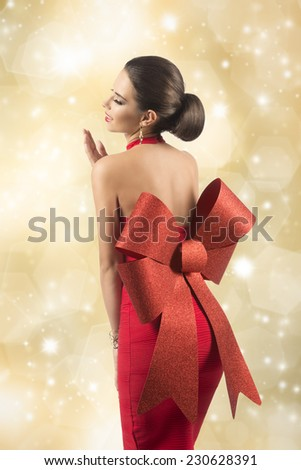 glamour woman with brown elegant hair-style wearing sexy red christmas dress with big glitter bow, posing turned on her naked back and smiling  - stock photo