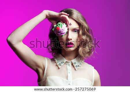 Glamour woman with cake and glamour make up over bright pink background. Fashion photo. - stock photo