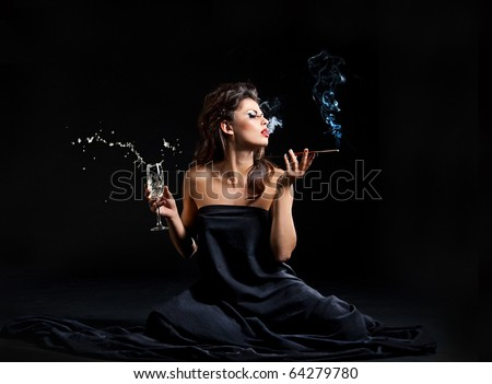 Glamour women with champagne and cigarette on black - stock photo