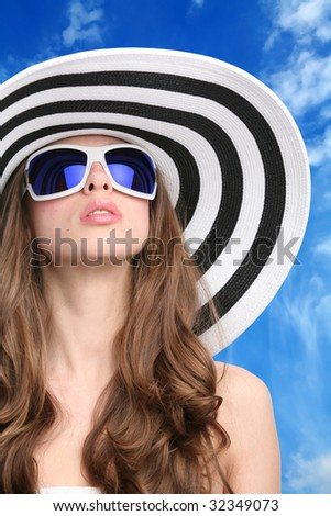 glamourous girl in striped hat and sunglasses on background of the blue sky