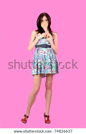 glamourous girl wearing colorful dress with lollipop