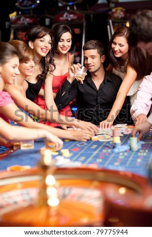 glamourous laughing friends plying betting at roulette table - stock photo
