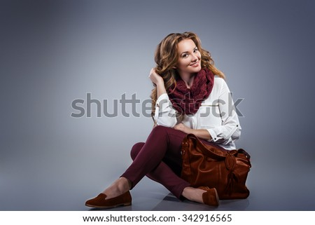 Glamourous portrait of the young beautiful woman in leather boots and stylish handbag. Trend fashion look.Portrait of beautiful blonde young woman posing with fashionable bag. - stock photo