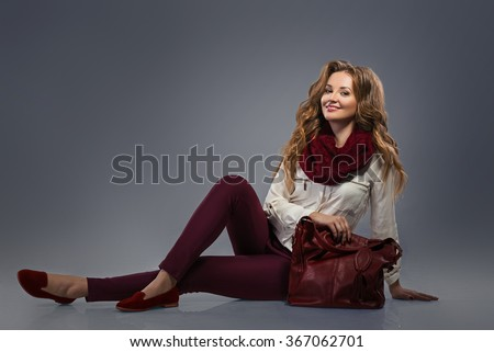 Glamourous portrait of the young beautiful woman in leather boots and stylish handbag. Trend fashion look. - stock photo