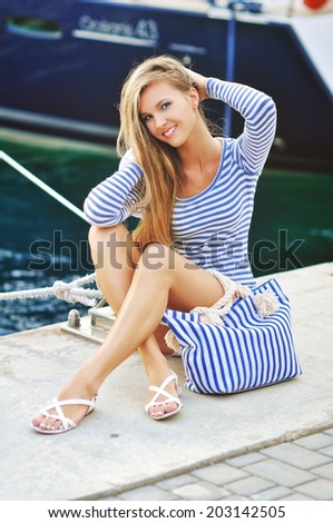 glamourous portrait of the young beautiful woman in leather sandals on the bank of a beach - stock photo