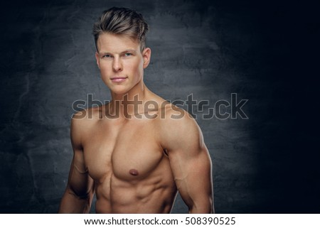 Glare portrait of shirtless athletic young male on grey background.