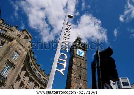 Glasgow's Merchant City entrance showing its sign and the Tron steeple with a blue sky and clouds.