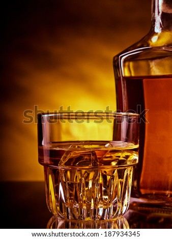 Glass and a bottle of whisky against red and yellow background - stock photo