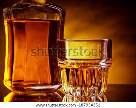 Glass and a bottle of whisky against red and yellow background