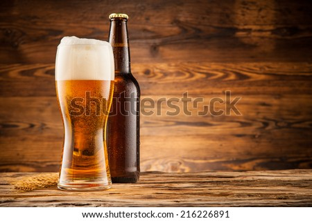 Glass and bottle of beer with wheat ears on wooden planks - stock photo