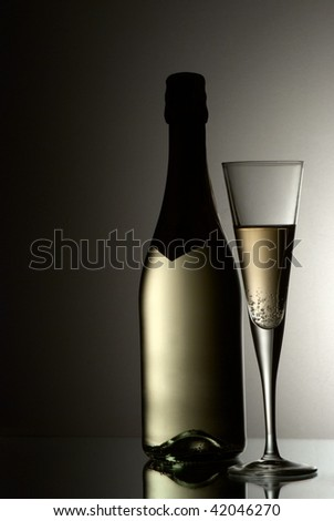 Glass and bottle of champagne against gradient background - stock photo