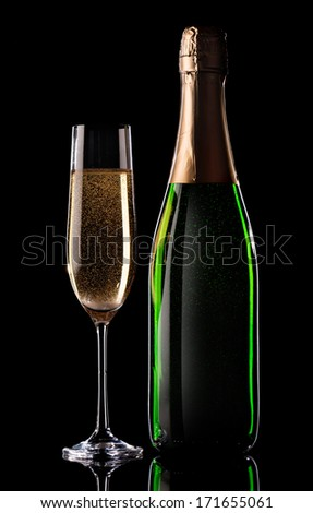 Glass and bottle of champagne on black background - stock photo