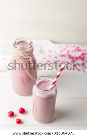 Glass and bottle of cherry smoothie isolated on white background