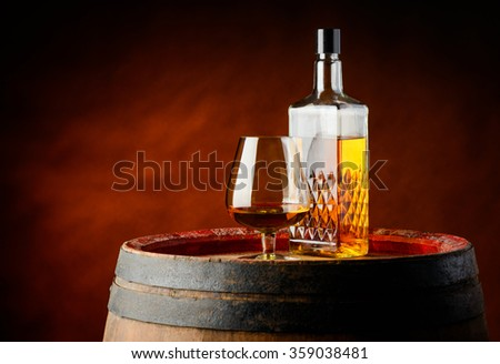 Glass and bottle of cognac brandy on a wooden barrel - stock photo