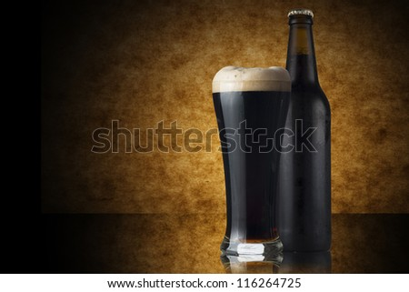Glass and Bottle of dark beer on yellow background - stock photo