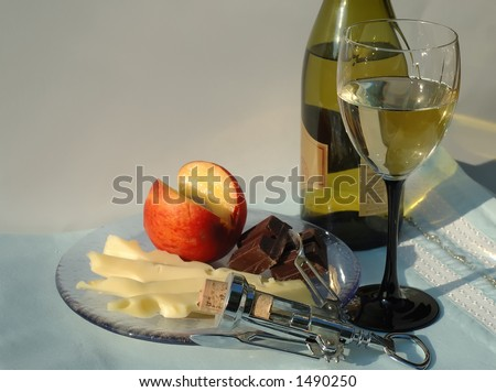 Glass and bottle of dessert white wine with cheese, chocolate and peach - stock photo