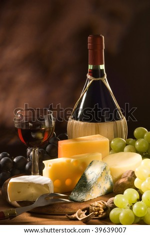 Glass and bottle of red italian wine with various types of cheese and garnishes - stock photo