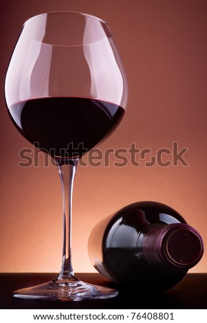 Glass and bottle of red wine, against a brown vignetting background. - stock photo
