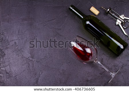 Glass and bottle of red wine on gray stone texture background. View from above, top studio shot - stock photo