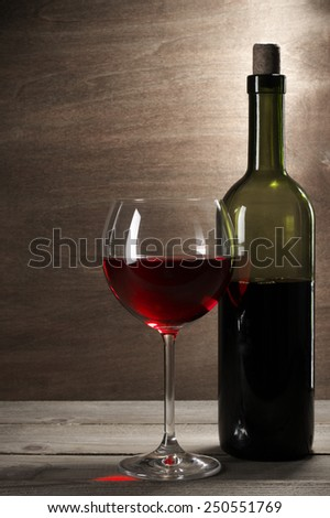 Glass and bottle of red wine on rustic wooden background.