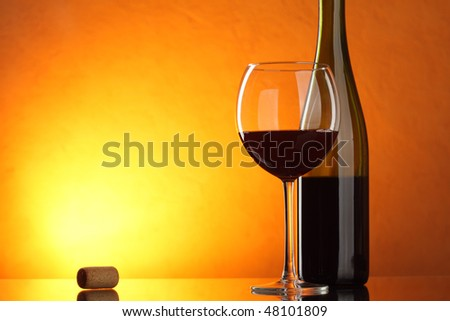 Glass and bottle of red wine on table