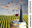 Glass and bottle of red wine on wood barrel with vineyard scene in the background - stock photo