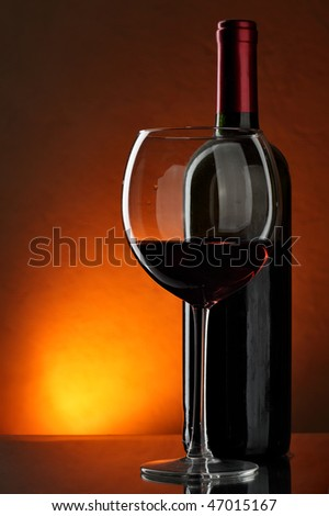 Glass and bottle of red wine over red background - stock photo